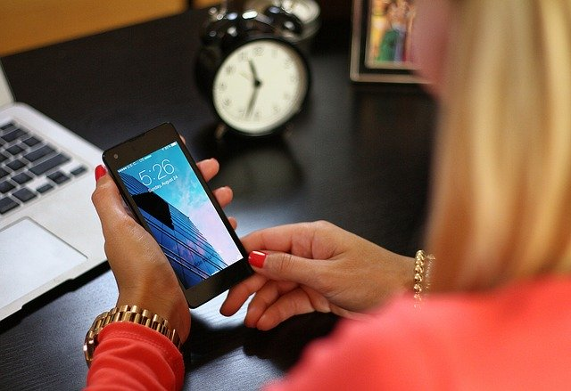 Pay bills on time - woman at desk with smartphone